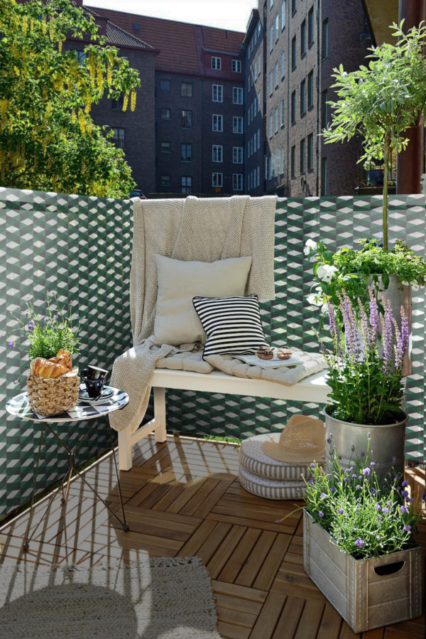 Designový balkon se stolkem, květinami a zástěnou během slunečného dne.