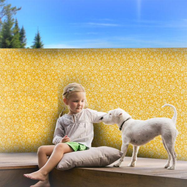 Holčička sedící na polštáři hladící pejska se zástěnou v pozadí