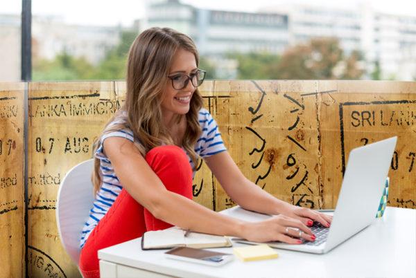 Usměvavá žena na počítači sedící na balkoně se zástěnou