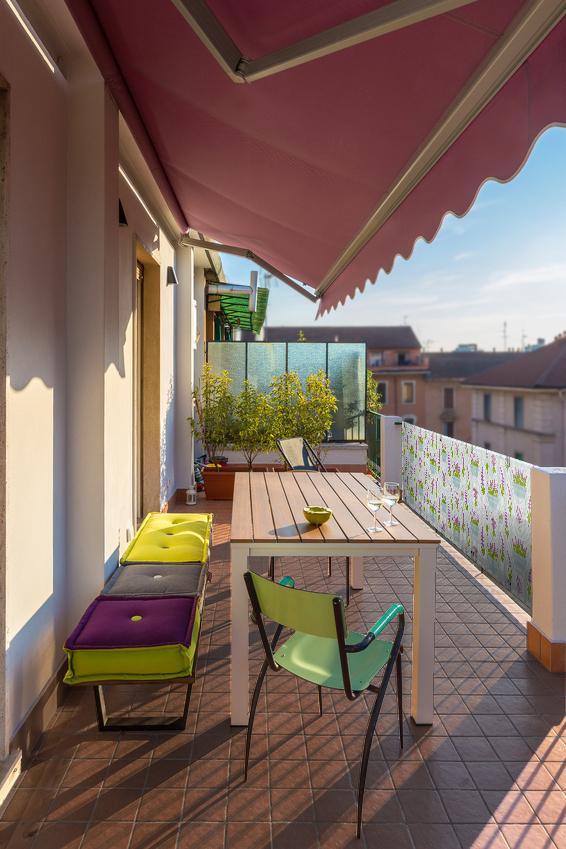 Prostorný balkon se stolem, židlemi, kytkami a zástěnou